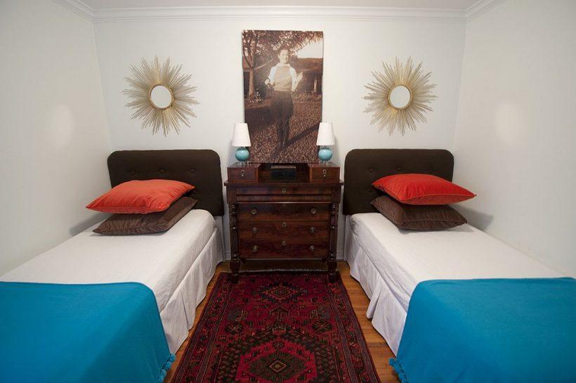 Ropa de cama y alfombras dan el color a esta pequeña habitación de invitados en blanco con dos camas individuales