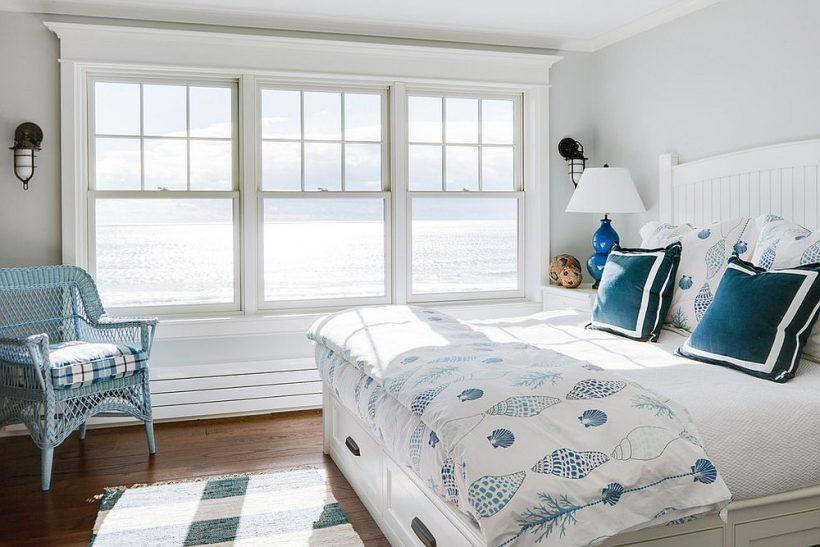 Poco ventoso dormitorio de estilo playa con un telón de fondo gris claro y detalles en azul elegante