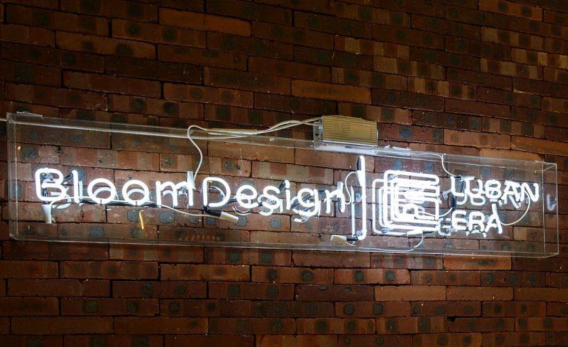 Logotipo del estudio del diseño de la floración brilla contra la pared de ladrillo telón de fondo