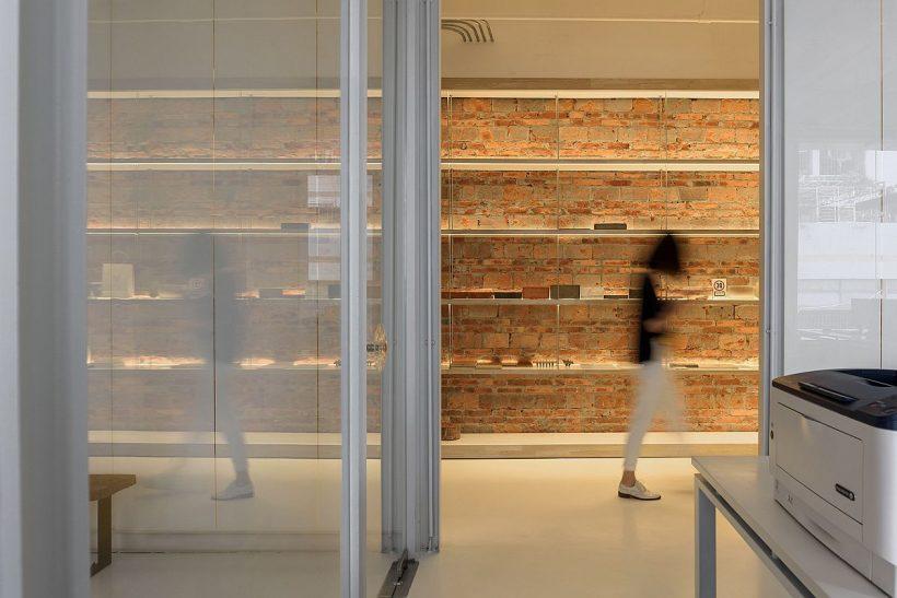 Pared de ladrillo rojo ofrece un contraste visual y de textura a un interior en blanco 1