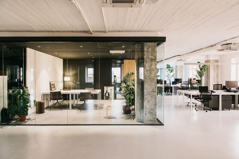 Exposed des piliers en béton et des murs en verre façonnent les espaces de bureaux privés