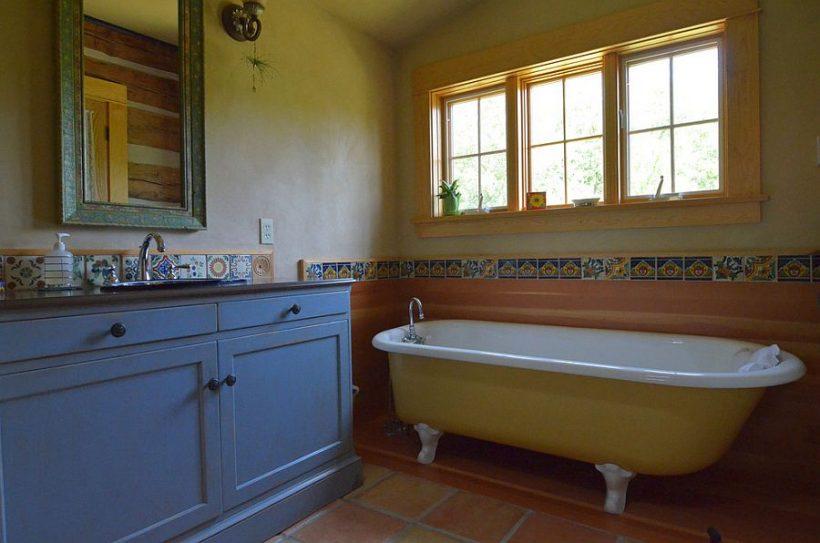 baño rústico con bañera con patas de color amarillo y la vanidad en azul