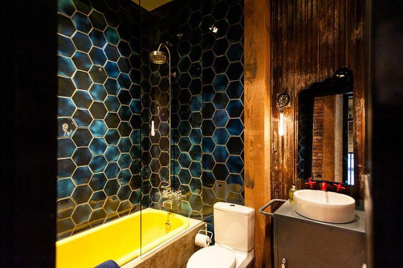 baño industrial ecléctica impresionante con baldosas hexagonales en negrilla y una bañera en amarillo
