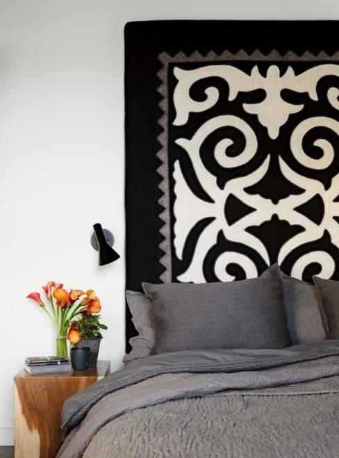Pendurar um tapete ou tapeçaria no lugar de uma cabeceira para um olhar artístico.