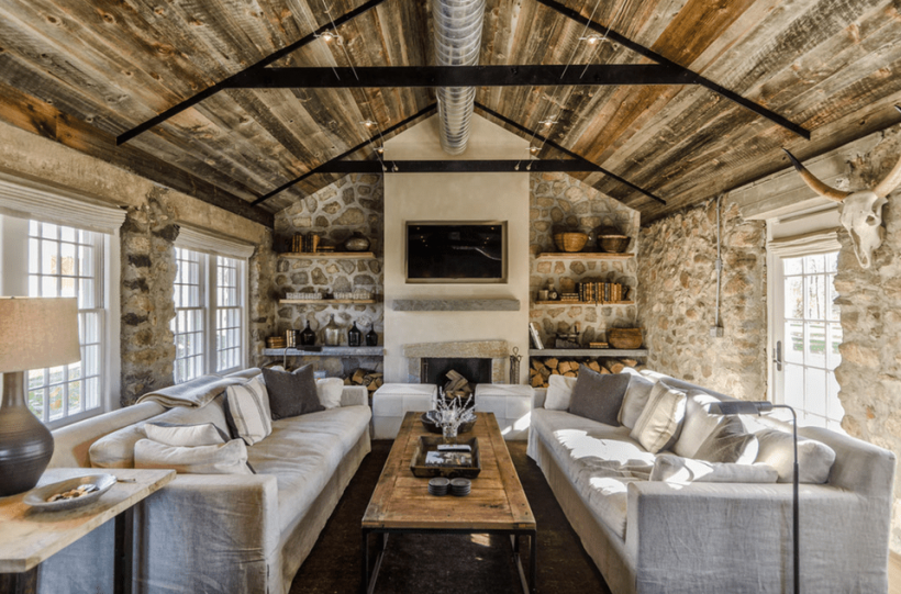 Farmhouse living room with stone walls reclaimed wood ceiling